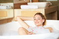 Woman relaxing in bubble bath smiling Stock Photo