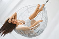 Woman relaxing in the chair young beautiful hanging with her hair down and legs up and smiling at camera Stock Photo