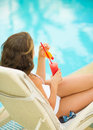 Woman relaxing on chaise-longue with cocktail Royalty Free Stock Images