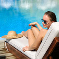 Woman relaxing in chaise lounge at the poolside Royalty Free Stock Image