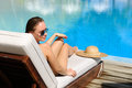Woman relaxing in chaise lounge at the poolside Stock Photography