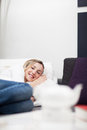 Woman relaxing in comfort on her bed taking a midday rest and smiling enjoyment at the camera Stock Photo