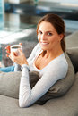 Woman relaxing on couch with cup of coffee Stock Photos