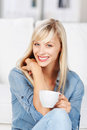 Woman relaxing with a cup of coffee beautiful long haired blonde on the sofa at home giving the viewer lovely smile Stock Image