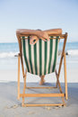 Woman relaxing in deck chair on the beach a sunny day Stock Photo