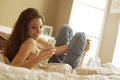 Woman relaxing on her bedroom relaxed at home reading a text message in bright Royalty Free Stock Images