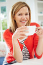 Woman relaxing at home with hot drink looking to camera smiling Stock Photos