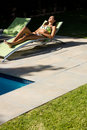 Woman relaxing on lounge chair at poolside Royalty Free Stock Photo