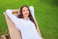 Woman relaxing in a lounger over green grass Royalty Free Stock Photography