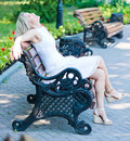 Woman relaxing on a park bench young Stock Images