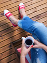 Woman relaxing on a patio wearing red sneakers and holding cup Royalty Free Stock Photo
