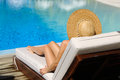Woman relaxing at the poolside in chaise lounge Stock Photo