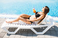 Woman relaxing at the poolside with cocktail. Summer time Royalty Free Stock Photo
