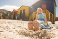 Woman relaxing on sand against huts at beach Royalty Free Stock Photo