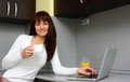 Woman relaxing smiling beautiful drinking coffee in kitchen with glass of orange fresh juice and laptop computer Stock Photo