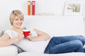 Woman relaxing on a sofa with a red mug pretty young blond of coffee or tea in her hands smiling at the camera Stock Photos