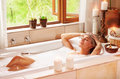 Woman relaxing at spa resort lying down in the bath with closed eyes and make a compress pleasure and healthy lifestyle Stock Images