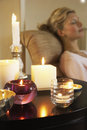 Woman relaxing by table with lit candles closeup side view of a on sofa beside Stock Photography