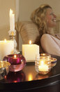 Woman relaxing by table with lit candles closeup side view of a on sofa beside Royalty Free Stock Photo