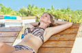 Woman relaxing in tropical resort young on beach chair and Royalty Free Stock Images