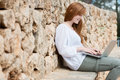 Woman relaxing typing on her laptop against a stone wall a ledge sitting computer balanced lap Stock Image