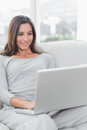 Woman relaxing and using her laptop sat on a couch Royalty Free Stock Photos