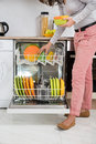 Woman removing bowls from dishwasher standing in kitchen Stock Images