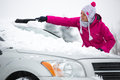 Woman removing snow from car windshield of her Stock Photography