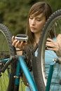 Woman repairs bike Royalty Free Stock Photo