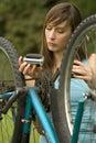 Woman repairs bike Royalty Free Stock Photo