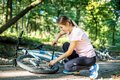 A woman repairs wheel of a bicycle. The concept of cycling and a Royalty Free Stock Photo