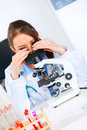 Woman researcher using microscope. Close-up Royalty Free Stock Image