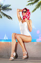 Woman in resort place white bathing suit and red scarf on embankment of Stock Photos