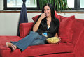 Woman resting in living room eating popcorn Stock Photo