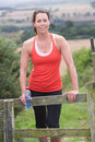 Woman resting during run in countryside smiling to camera Royalty Free Stock Images