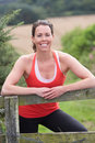 Woman resting during run in countryside smiling to camera Royalty Free Stock Photography
