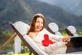 Woman resting on the sunbed young and cute in sweater with heart shape lying in mountain resort high contrast image with small Royalty Free Stock Photo