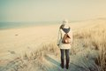 Woman with retro backpack on the beach looking at the sea Royalty Free Stock Photo