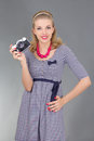 Woman in retro clothes with photo camera over grey Stock Photo