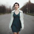 Woman with retro coiffure walking street wearing white coat Royalty Free Stock Photos