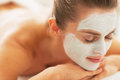 Woman with revitalising mask on face laying on massage table relaxed young Royalty Free Stock Photo