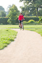 Woman rides a bicycle around the city park Royalty Free Stock Photos