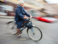 Woman rides a bicycle through the streets abstract image of mature intentional motion blur Stock Photo