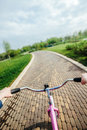 Woman riding a bicycle in park handlebar view pink Royalty Free Stock Photos