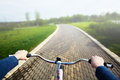 Woman riding a bicycle in park, handlebar view. Royalty Free Stock Photo