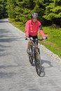 Woman riding bike on sunny cycling path mountain in forest Stock Images