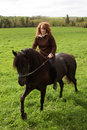 Woman riding horse in field Stock Photo