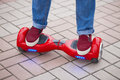 Woman riding on modern red electric mini segway or hover board scooter Royalty Free Stock Photo