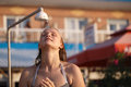 Woman rinsing of at the beach under a shower beautiful young fresh water salt and sand off her body with her eyes Stock Photo