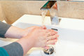 Woman rinsing her hands in sink with water Royalty Free Stock Photos